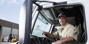 Truck driver (30s) sitting in cab of semi-truck.